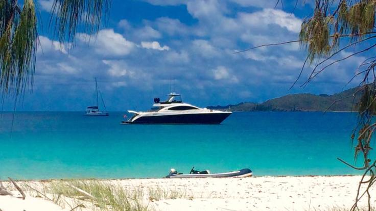 Luxury Hamilton Island charter boat moored off the beach in the Whitsunday Islands