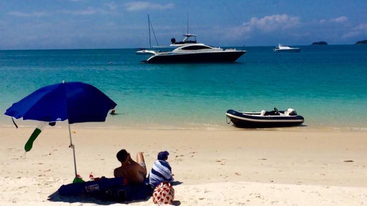 A picnic on the beach in the Whitsunday Island with your motor yacht moored offshore