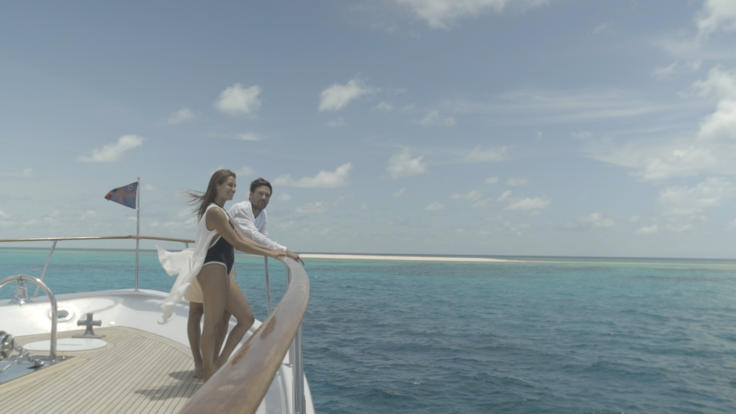 Couple on the bow of Super Yacht on the Great Barrier Reef in Australia