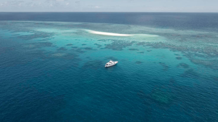 Aerial view of Super Yacht moored on the Great Barrier Reef off Port Douglas
