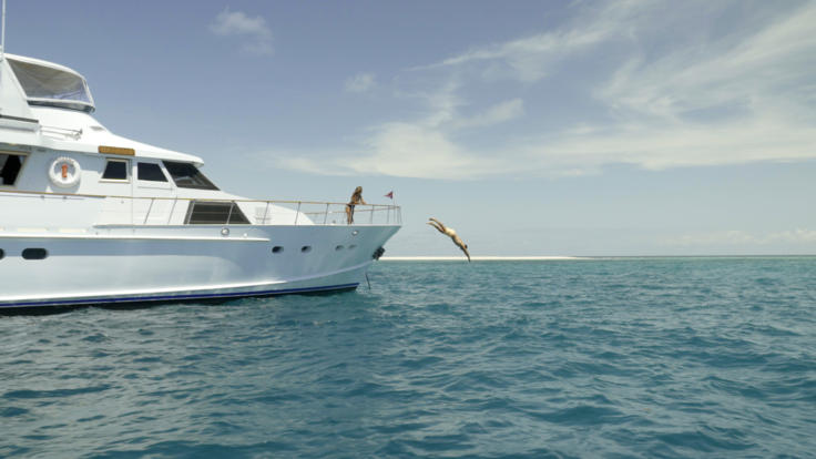 Guests diving off the bow of the Super Yacht on the Great Barrier Reef of Port Douglas