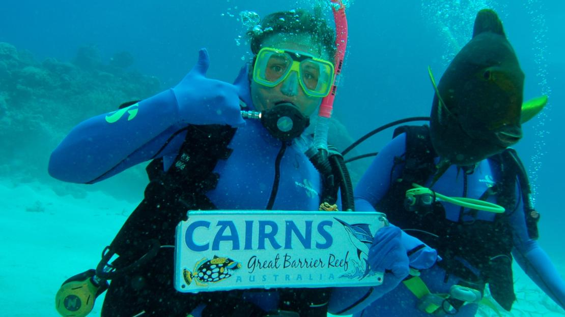 Holding a sign saying Cairns whilst scuba diving on the Great Barrier Reef