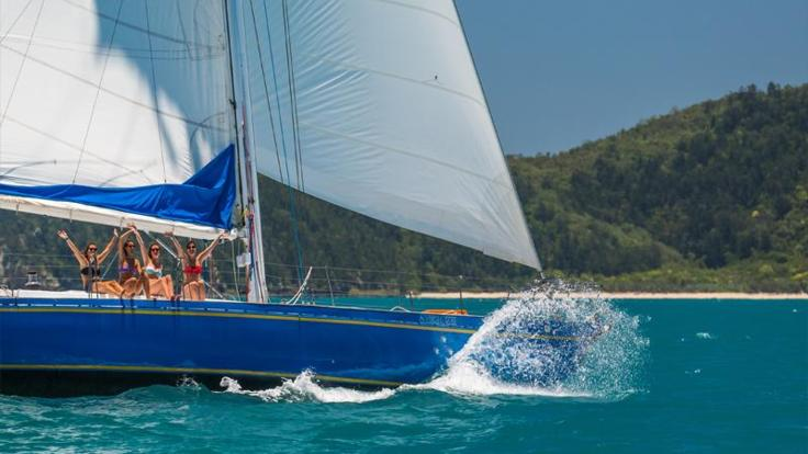 Hands up in excitement on Whitsundays sailing tour to Whitehaven Beach