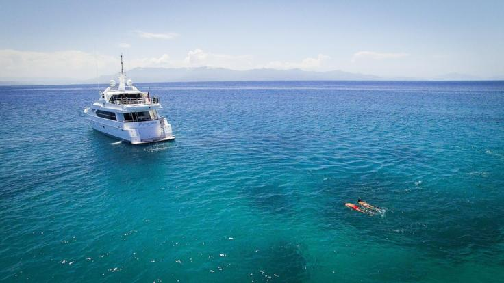 Couple snorkeling on the Great Barrier Reef - Superyacht moored in the background