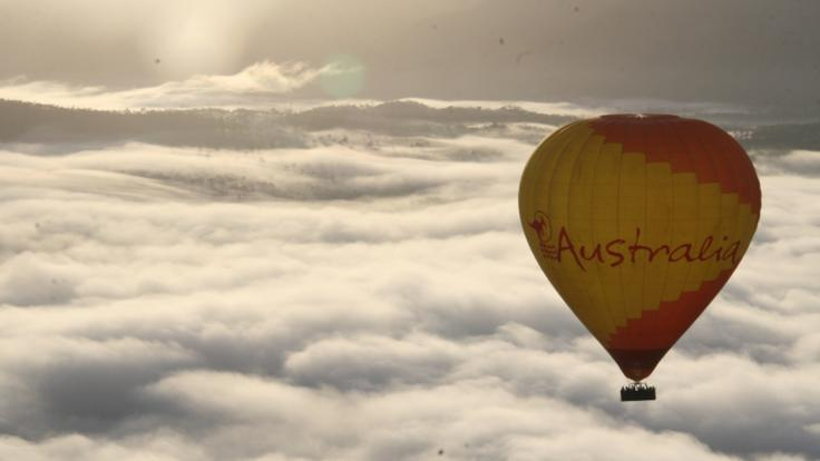 Ride the air currents in the hot air balloon above the clouds
