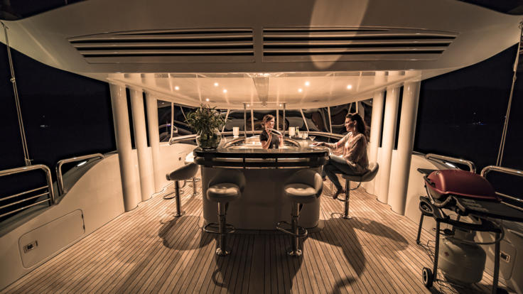 Guests relaxing upper deck at night on the Superyacht on the Great Barrier Reef in Australia