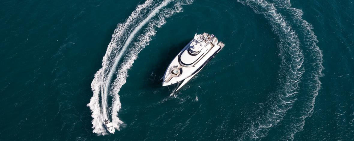 Aerial view of Superyacht on the Great Barrier Reef with tender circling the yacht