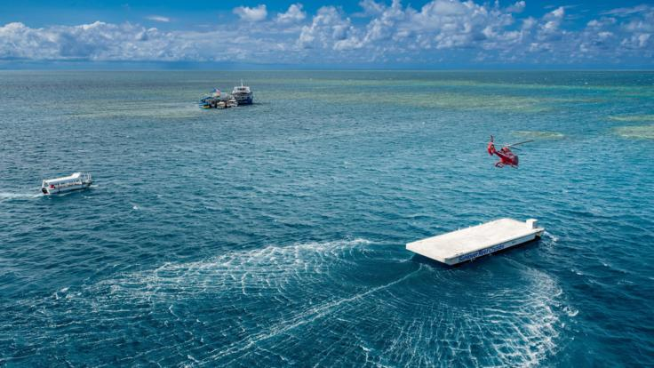 Helicopter landing on the pontoon on the Great Barrier Reef