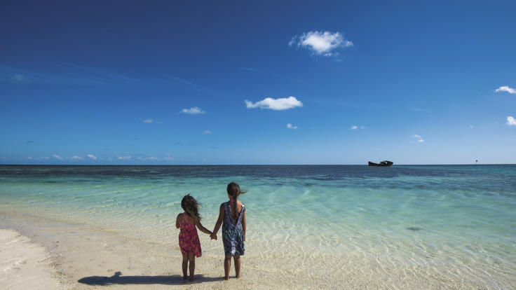 Kids enjoying the pristine beach and water on Heron Island, Great Barrier Reef